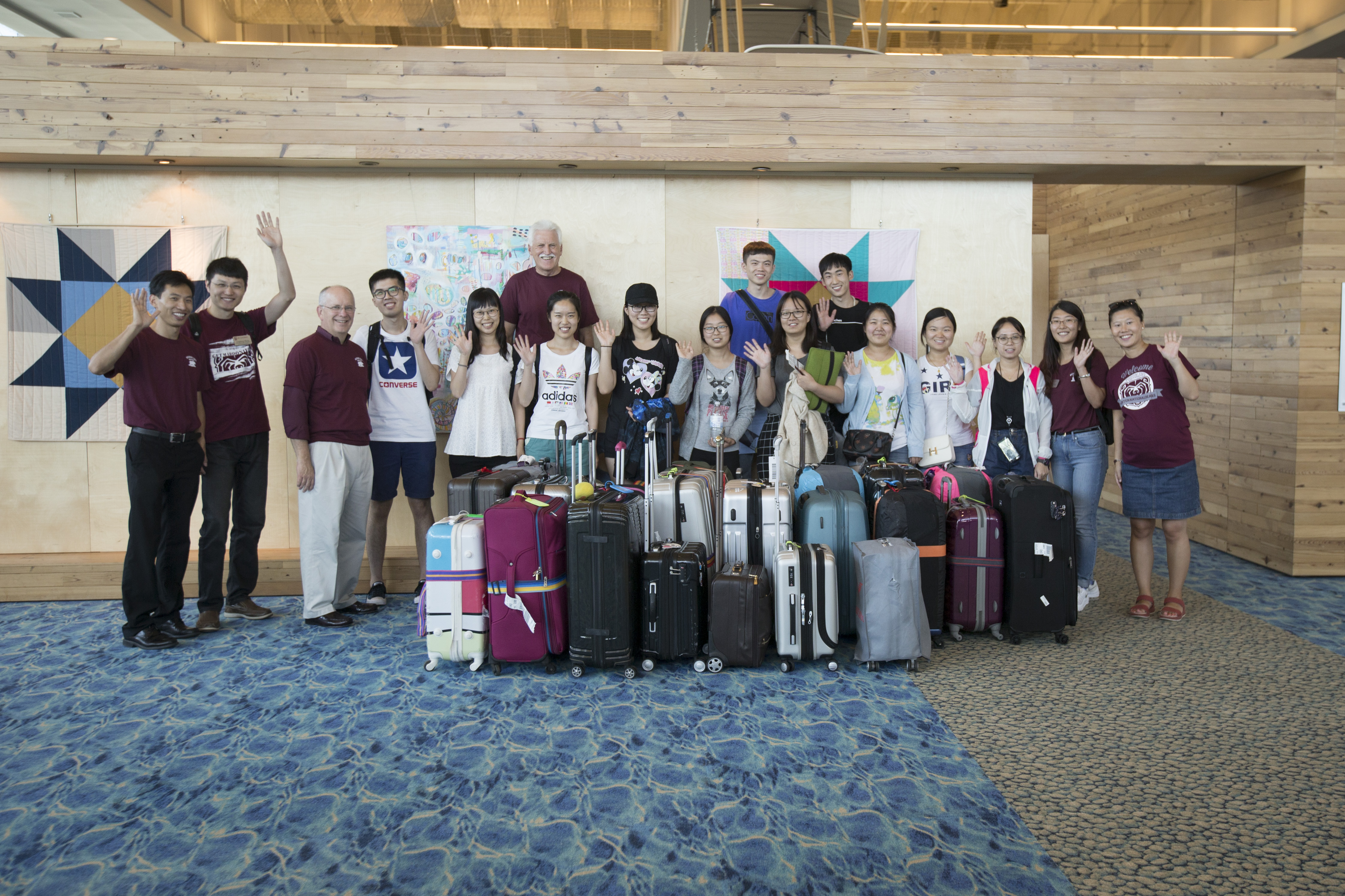 A group of students pose with luggage at the airport